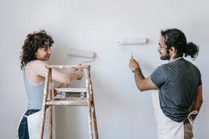 Una pareja pintando su casa